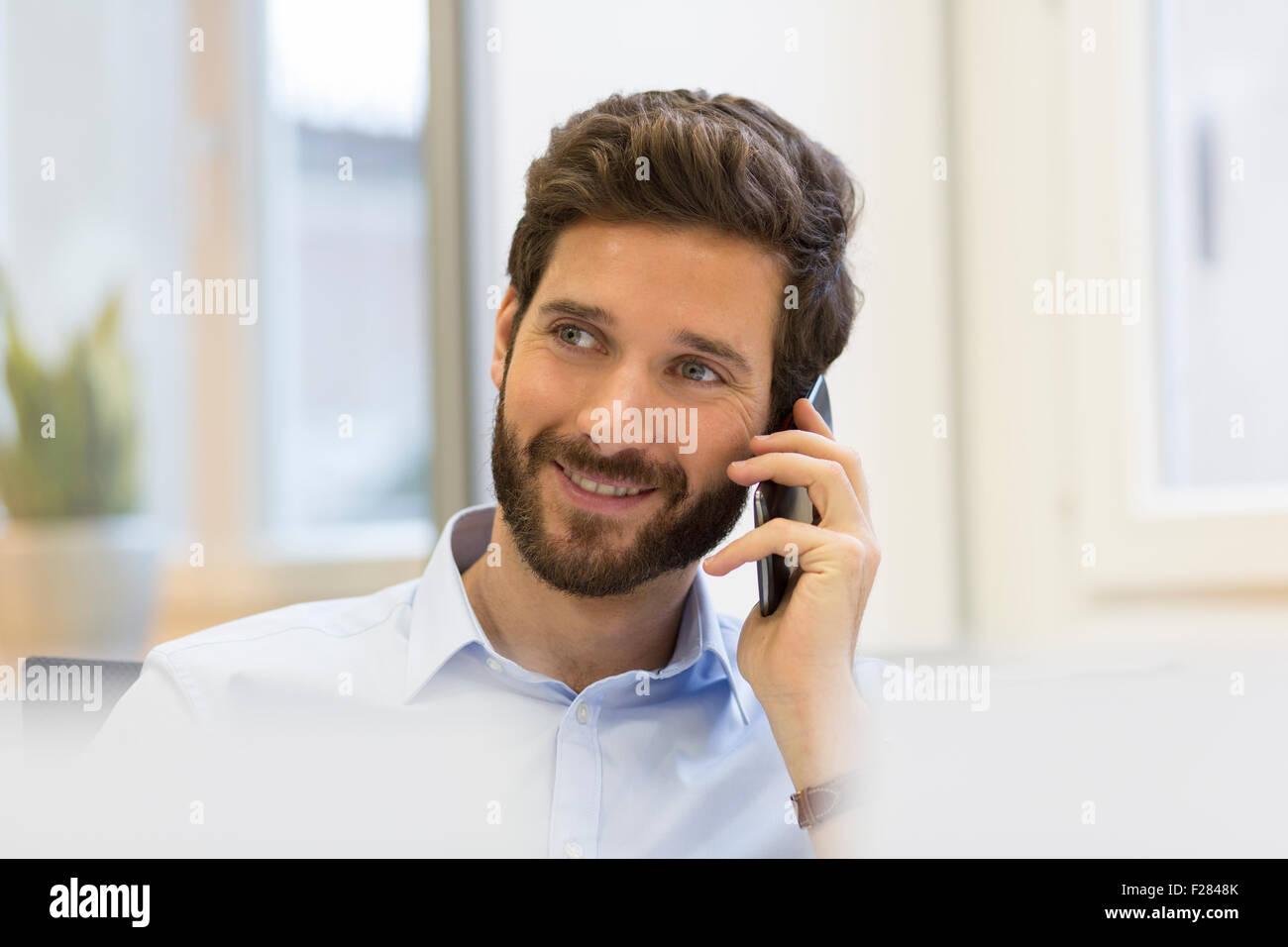 Bearded businessman talking on cell phone au bureau Banque D'Images