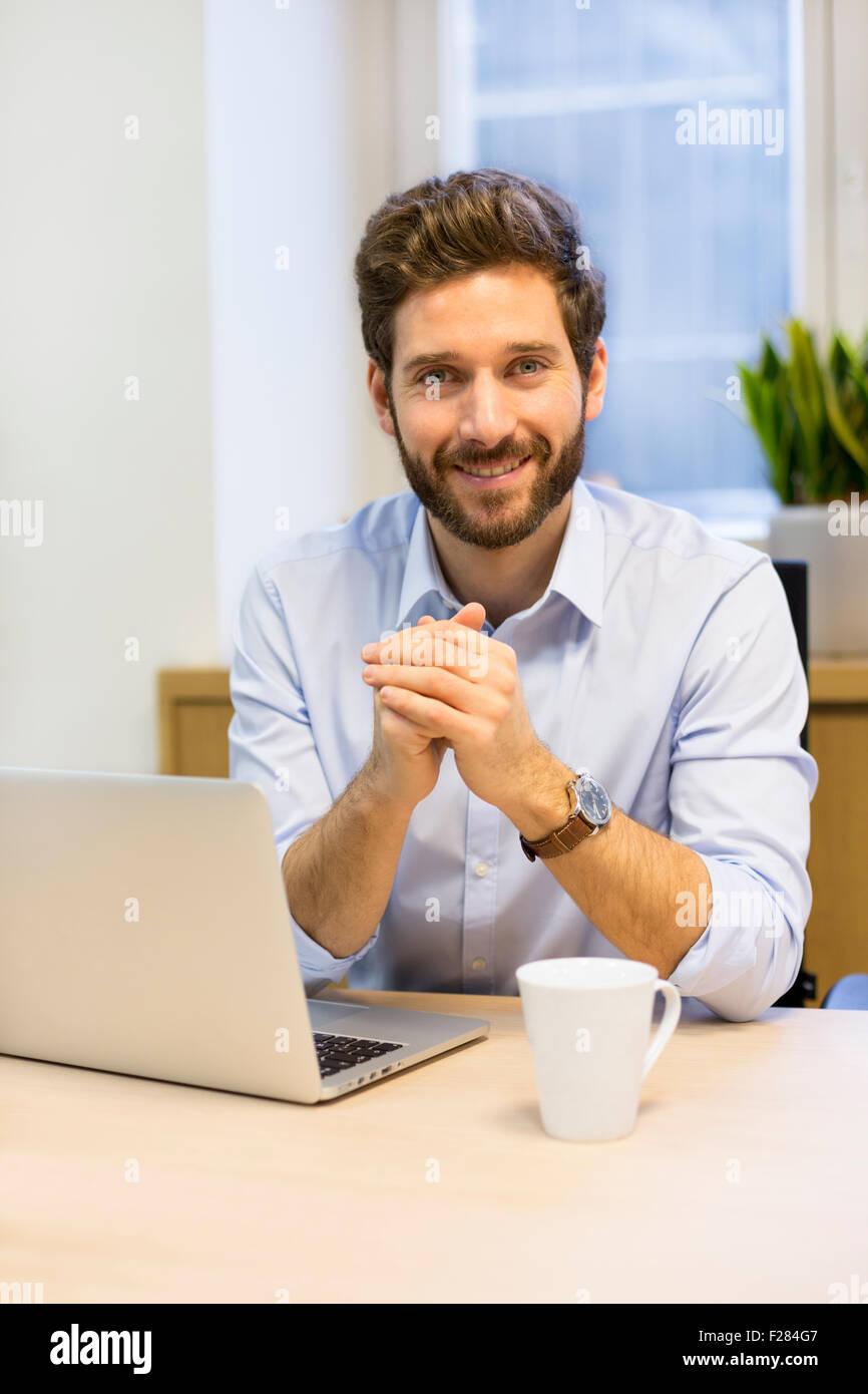 Businessman working on laptop at desk with hands clasped Banque D'Images