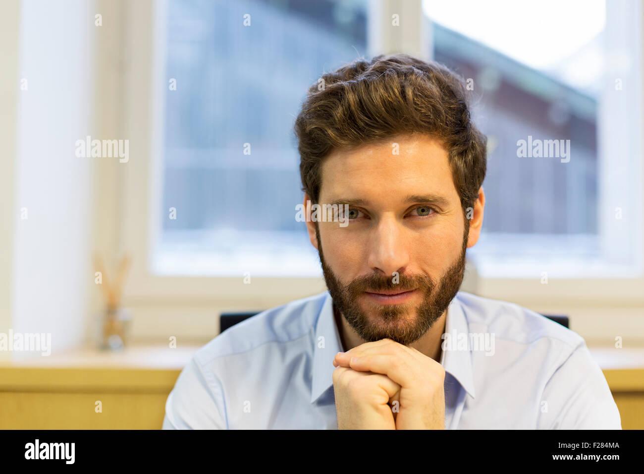 Portrait of businessman with hands clasped barbu Banque D'Images