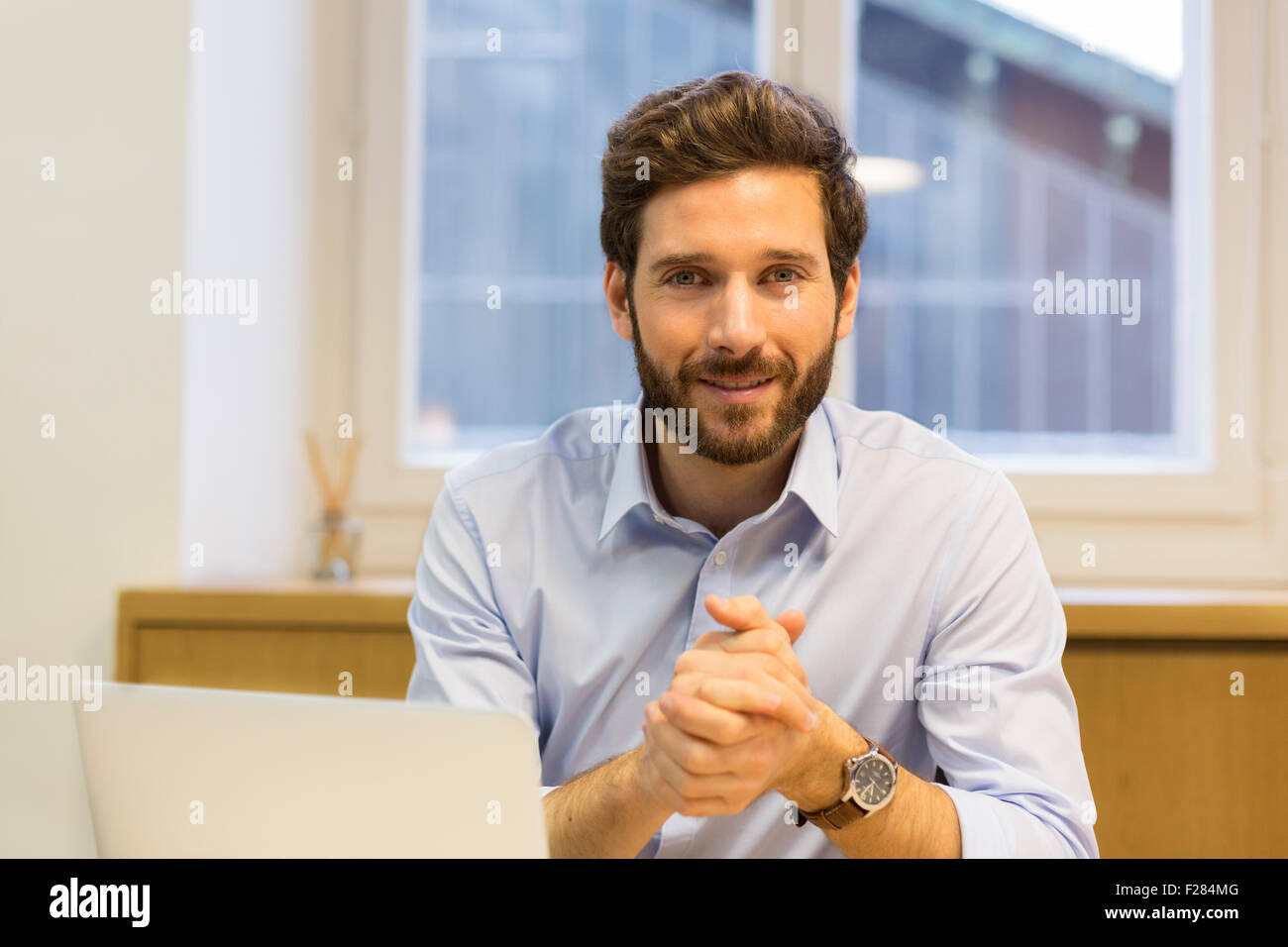 Confiant bearded businessman with hands clasped Banque D'Images