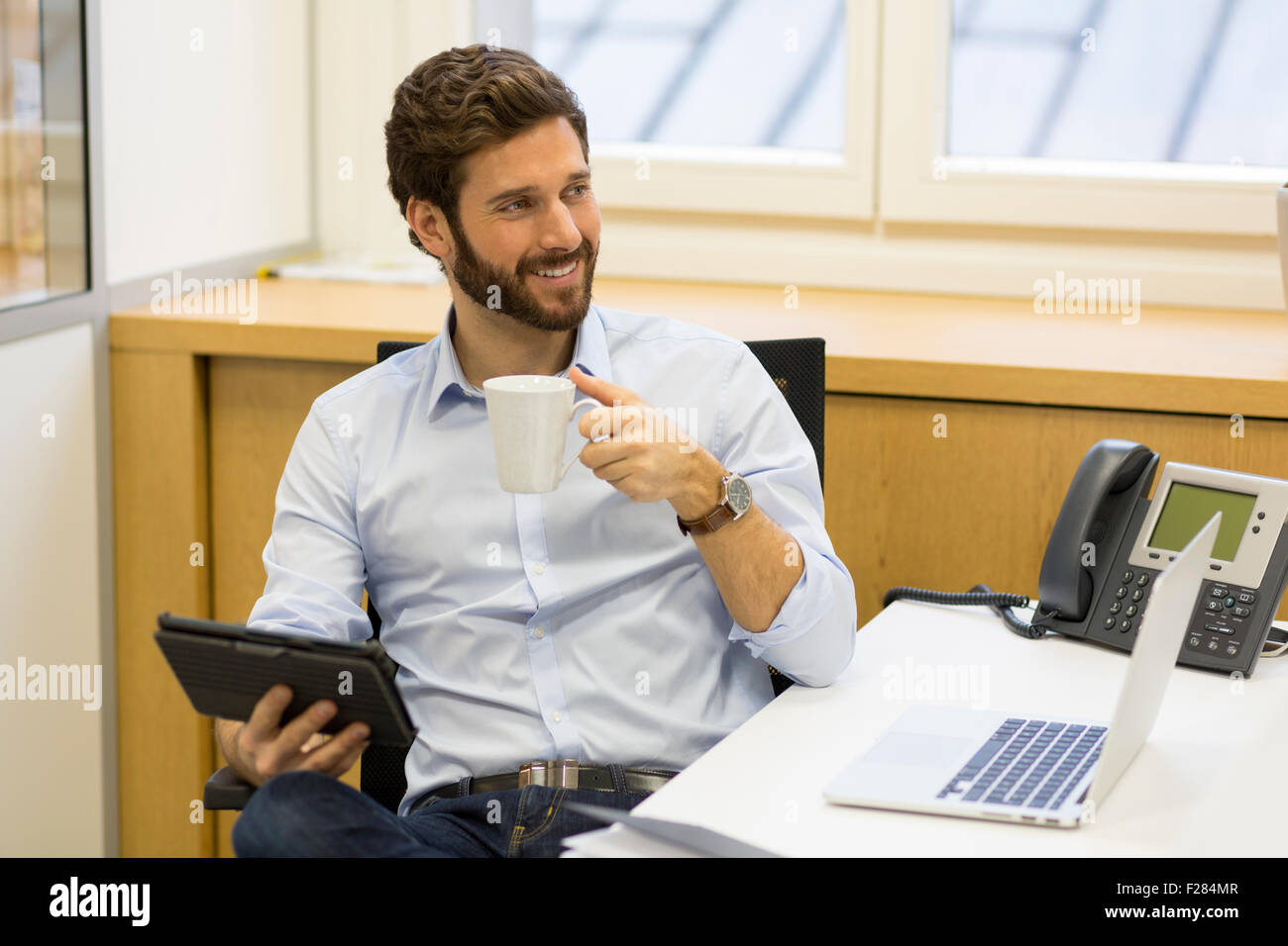 Portrait of smiling businessman holding Coffee cup in office Banque D'Images