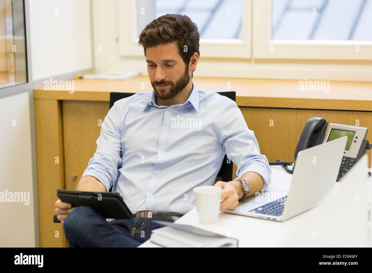 Portrait of businessman holding Coffee cup and using digital tablet in office Banque D'Images