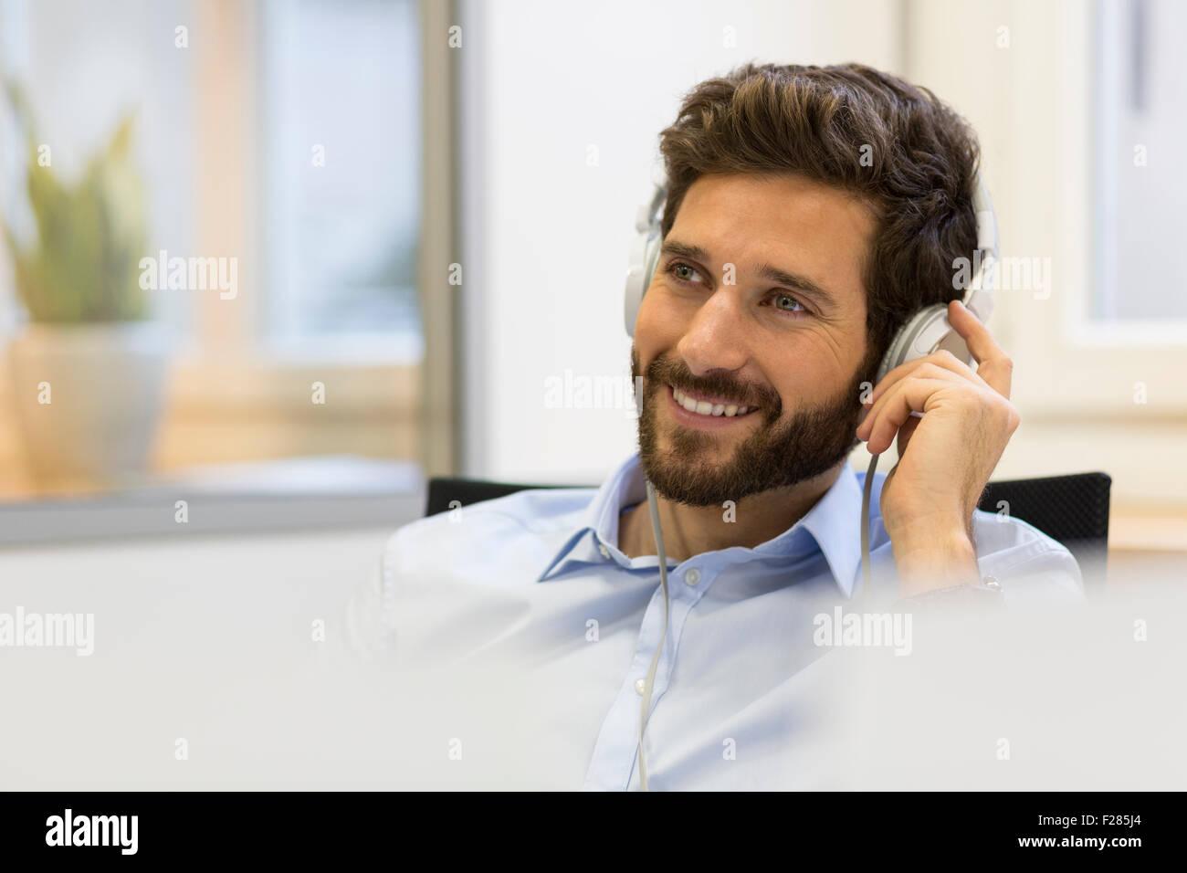 Smiling businessman écouter de la musique avec des écouteurs Banque D'Images
