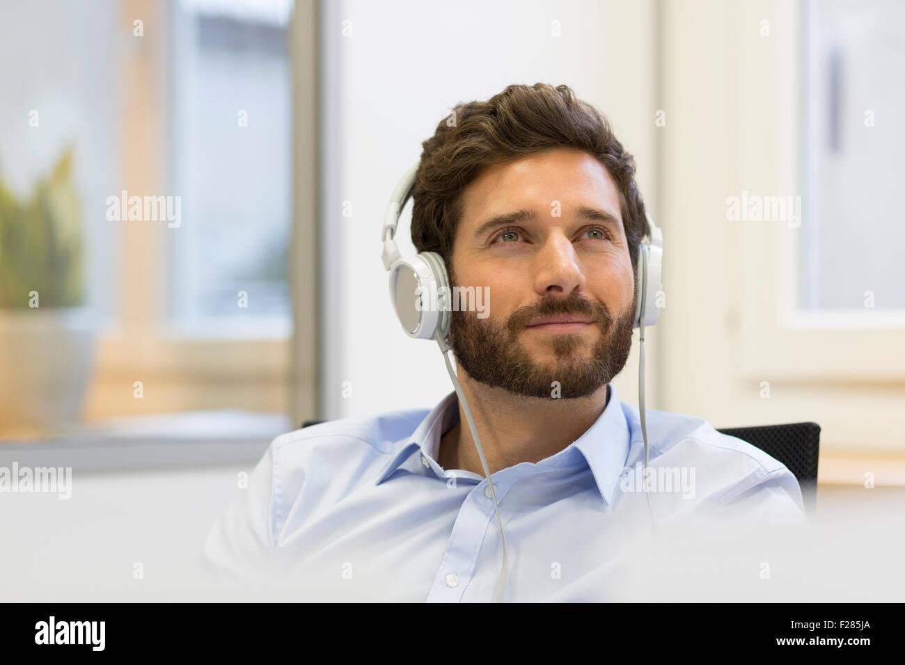 Pensive businessman écouter de la musique avec des écouteurs Banque D'Images