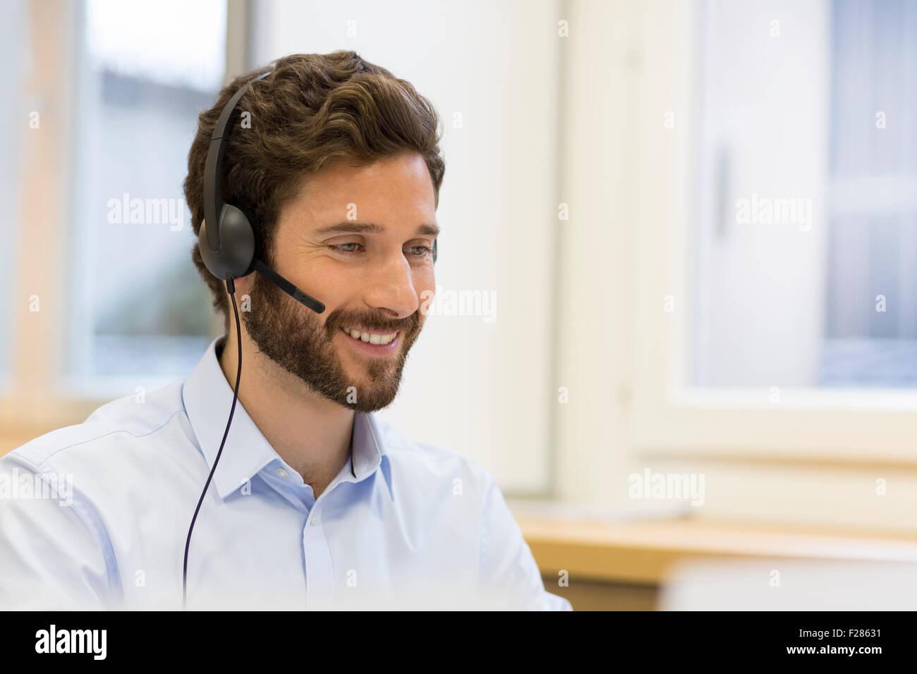 Homme barbu portant à l'aide de casque ordinateur Banque D'Images
