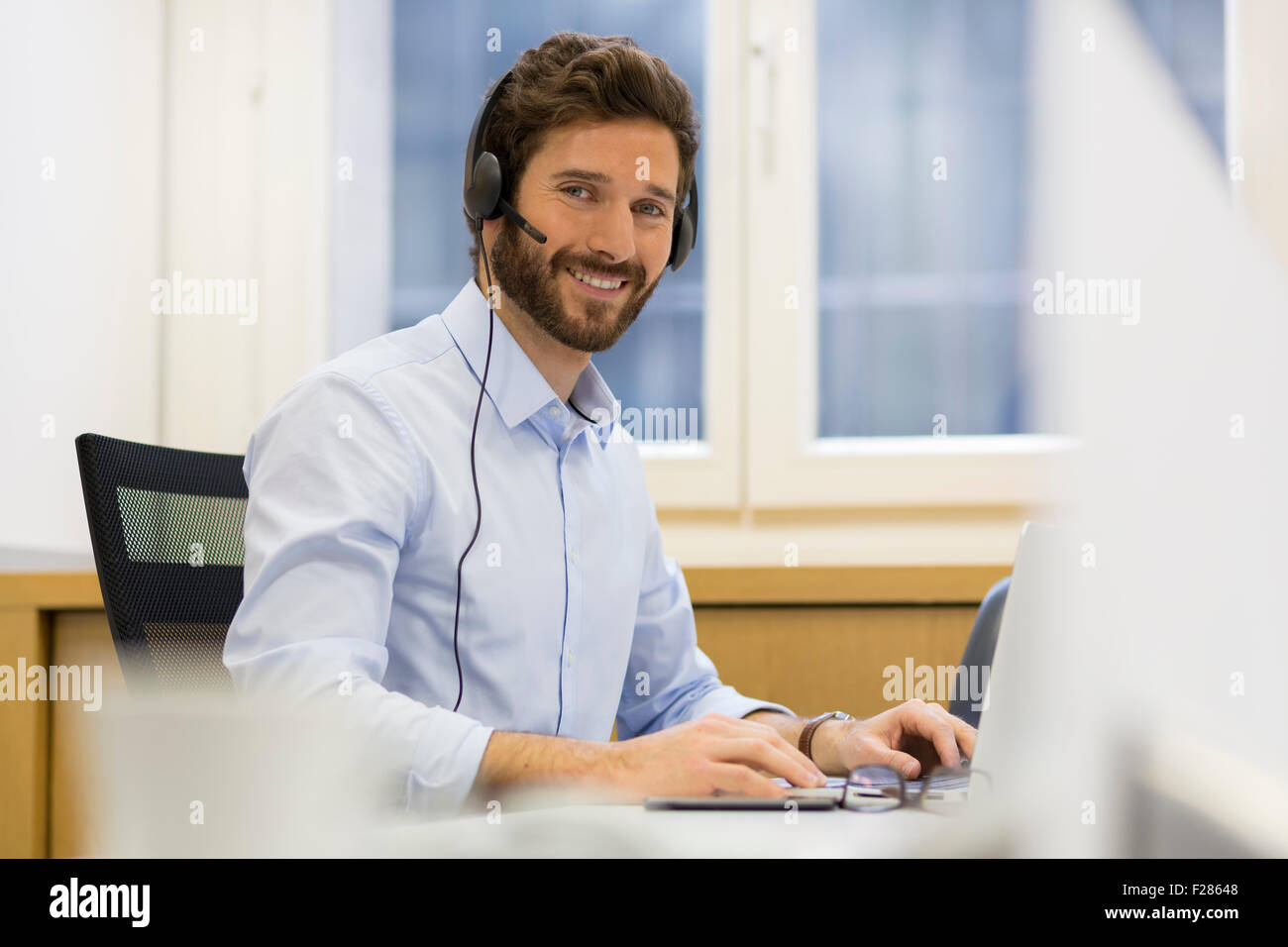 Smiling man wearing headset using laptop Banque D'Images