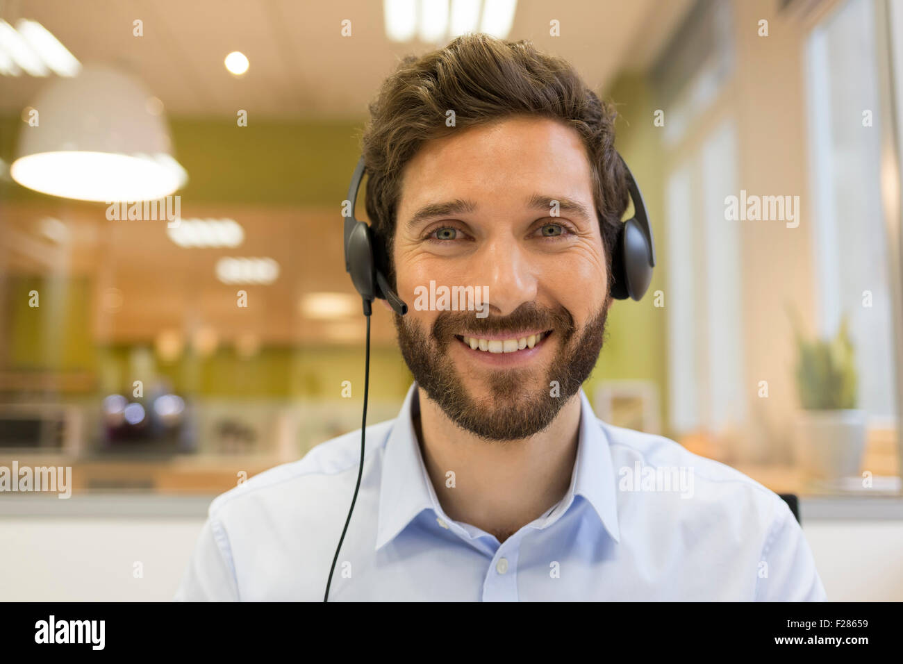 Portrait of smiling man wearing headset en open space Banque D'Images