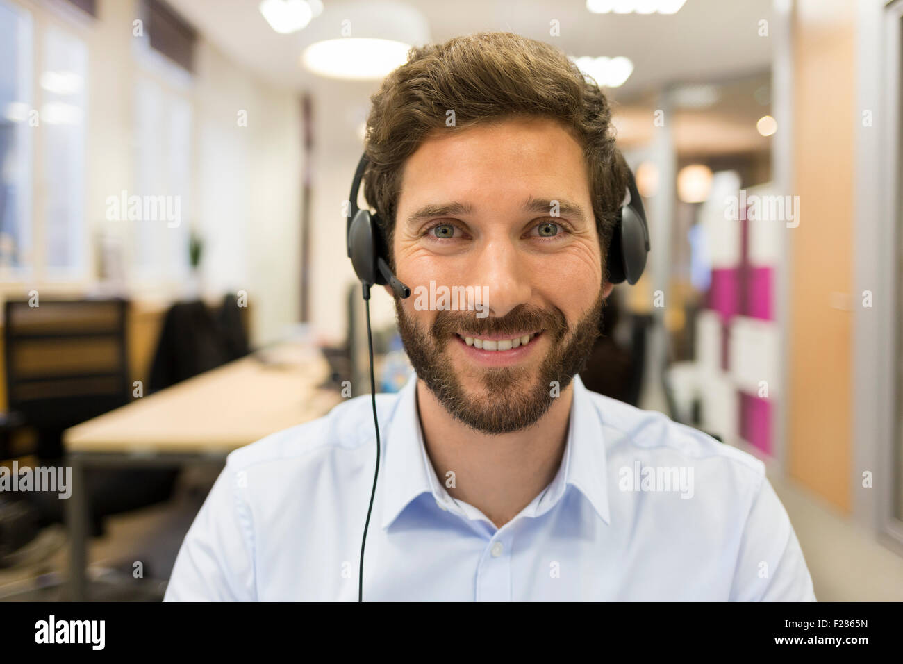 Portrait of smiling man wearing headset in office Banque D'Images