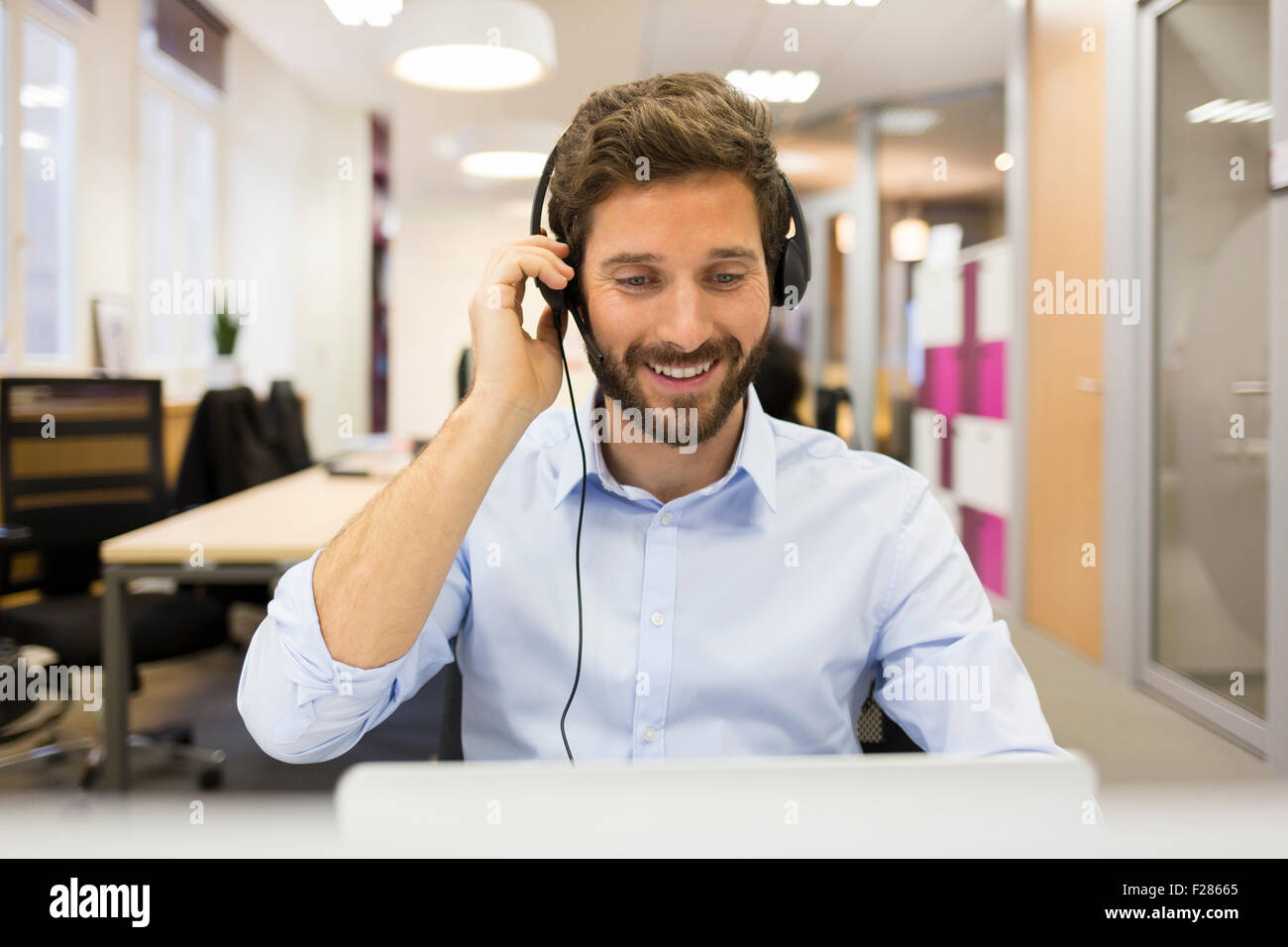 Portrait of smiling man wearing headset using laptop Banque D'Images