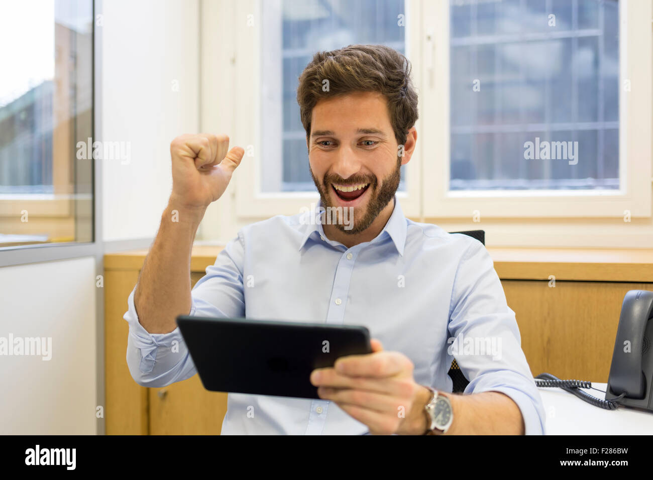 Cheering businessman with arms up using digital tablet in office Banque D'Images