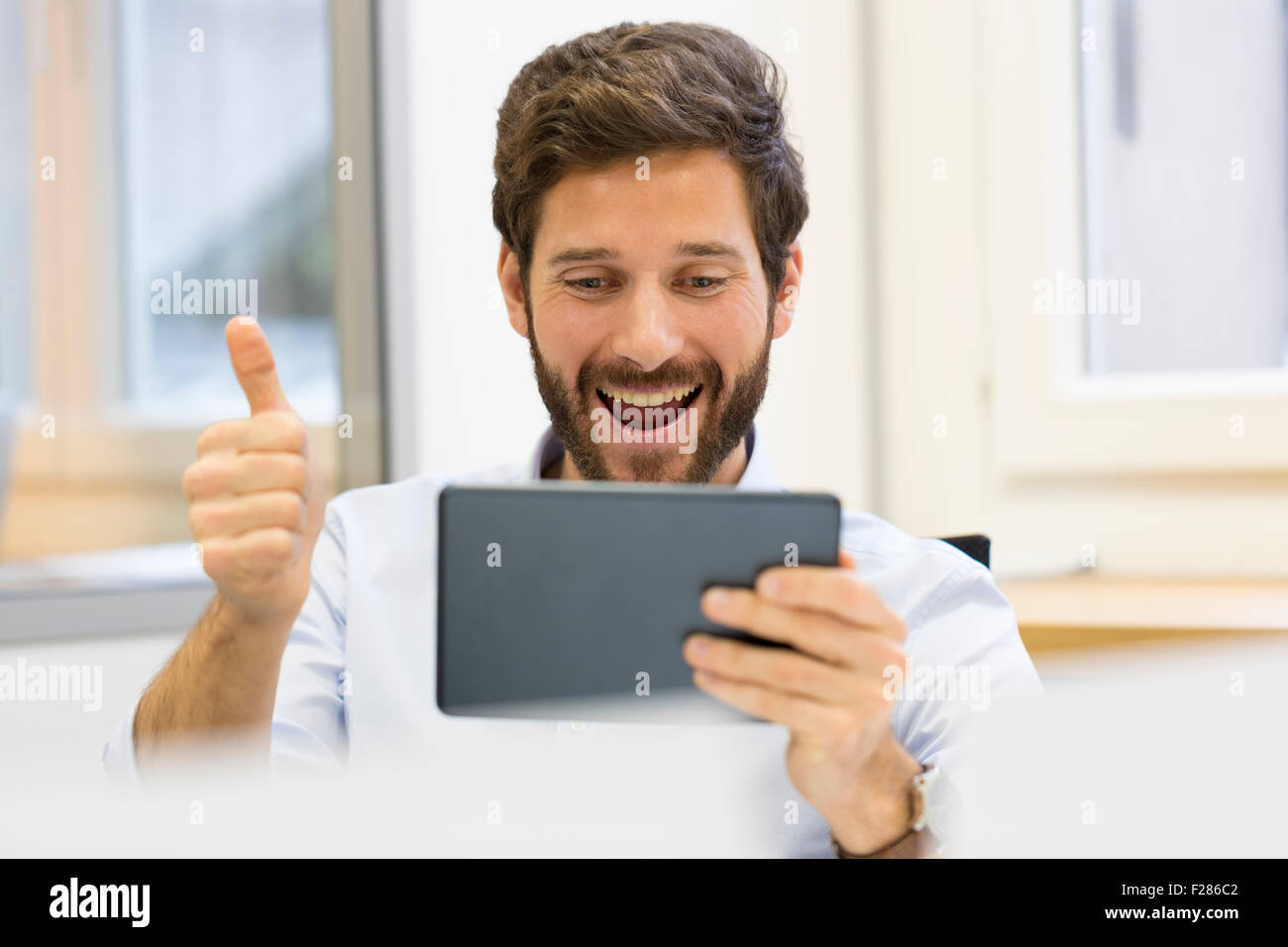 Cheering businessman with thumb up in office using digital tablet Banque D'Images