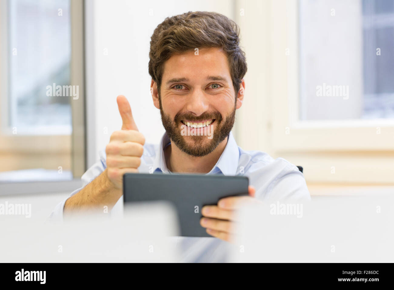 Happy businessman with thumb up in office using digital tablet Banque D'Images