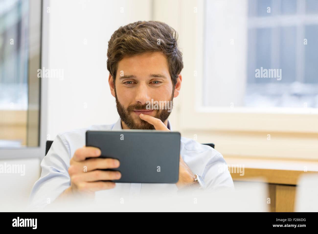 Pensive businessman using digital tablet in office Banque D'Images
