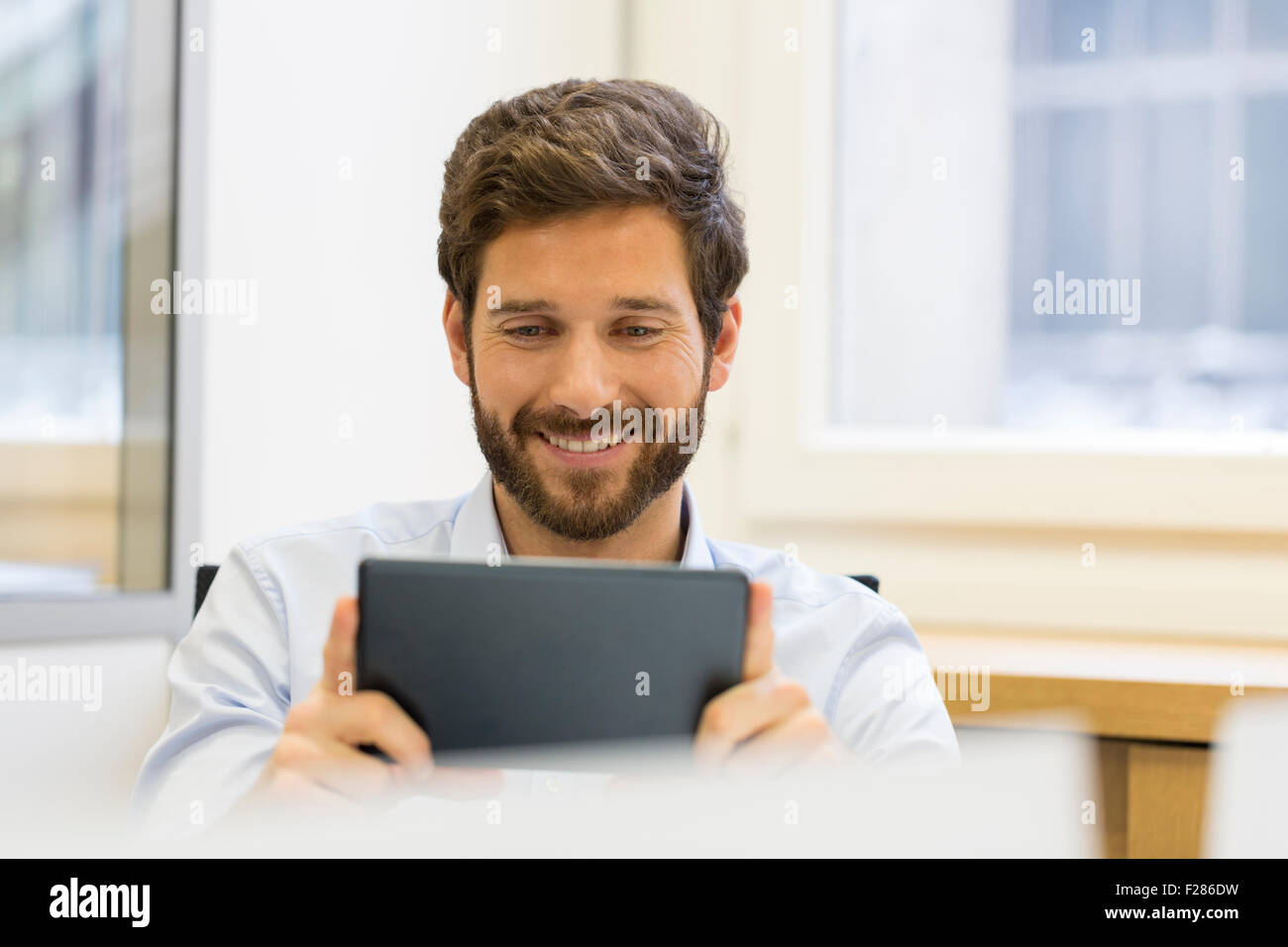 Cheering businessman using digital tablet in office Banque D'Images