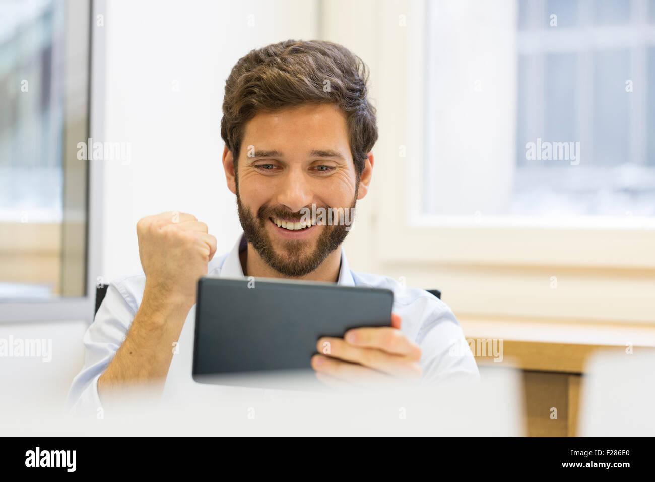 Homme d'acclamer avec perforation sous office using digital tablet Banque D'Images
