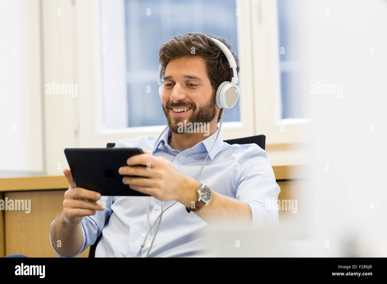 Creative businessman listening to headphones and using digital tablet Banque D'Images