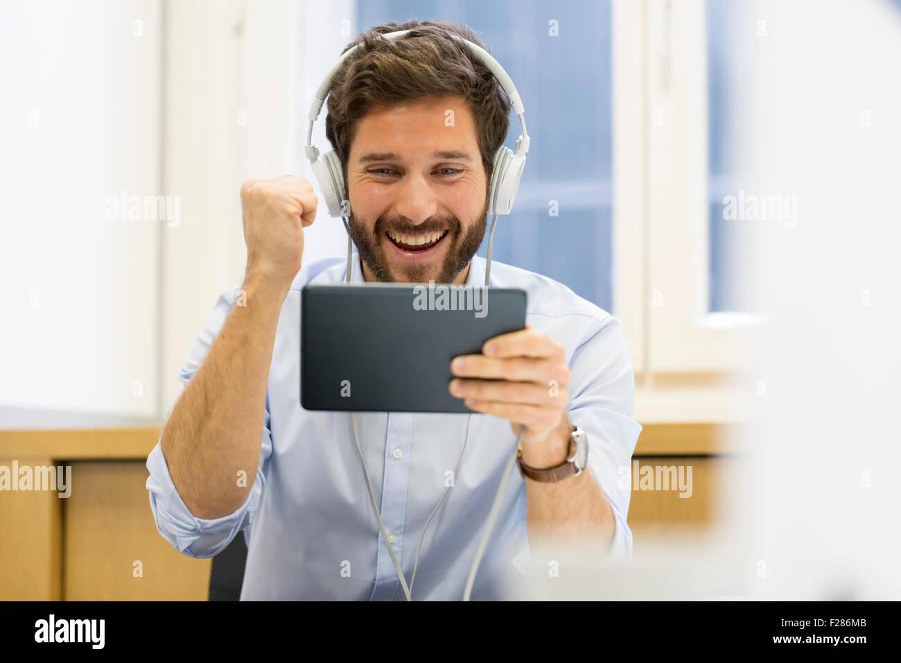 Creative businessman listening to headphones and using digital tablet avec le poinçon dans office Banque D'Images