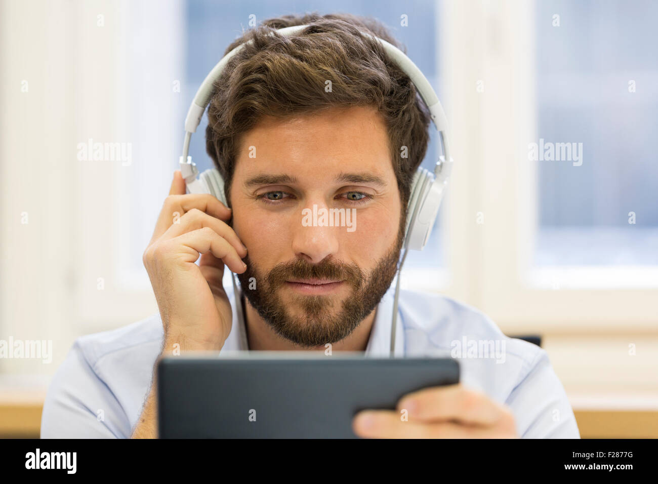 Creative businessman listening to headphones and using digital tablet. Banque D'Images