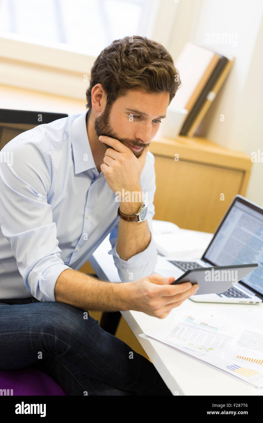 Jeune homme barbu en consultation en bureau ordinateur tablette. Banque D'Images