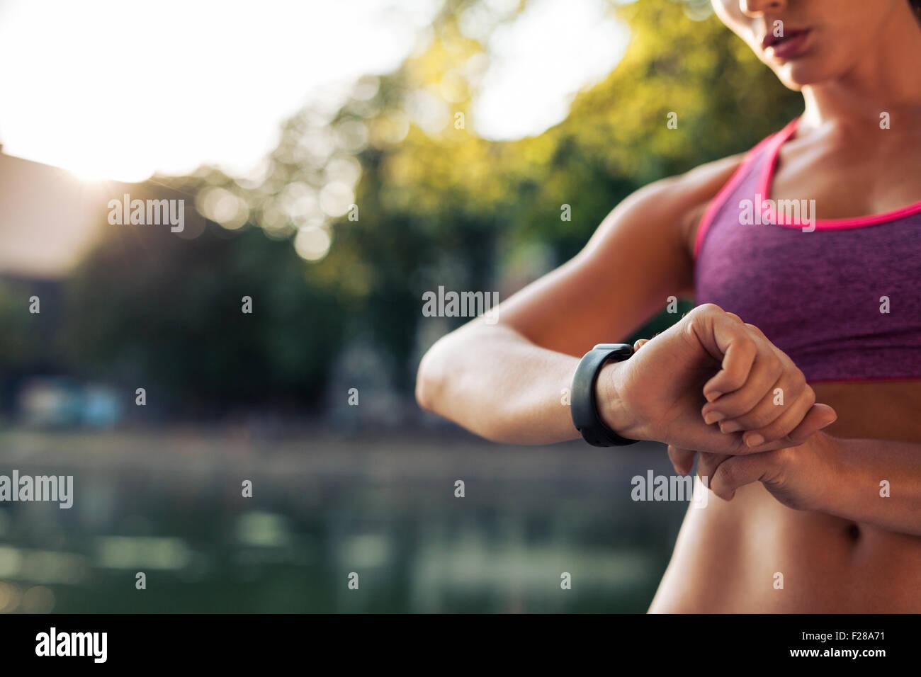 Femme mise en place de la smart watch remise en forme pour la course. Contrôle de l'appareil montre sportive. Photo Stock