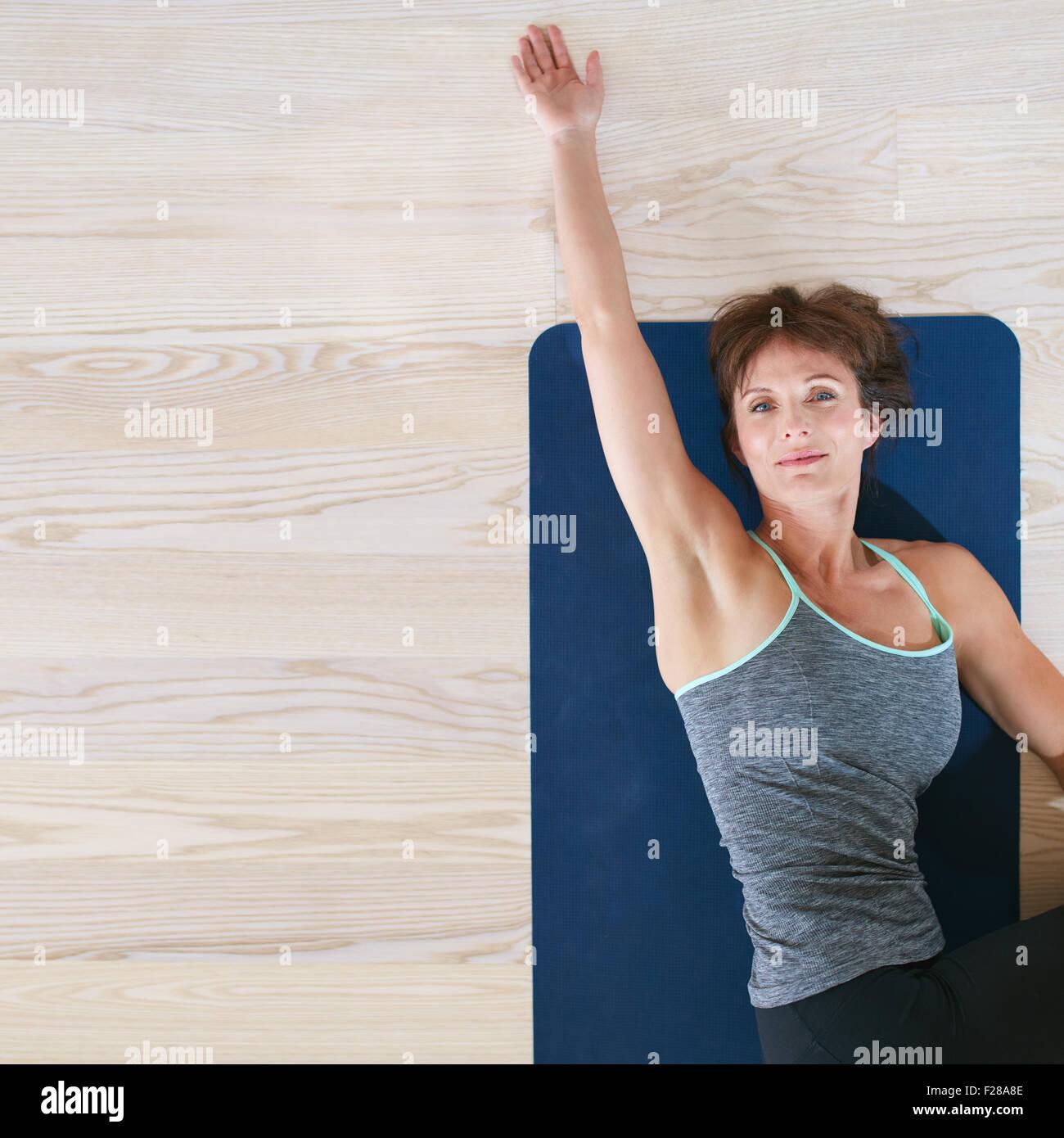 Vue de dessus de femme couchée et s'étendant sur des tapis d'exercice. Femelle sur marbre de tordre Photo Stock