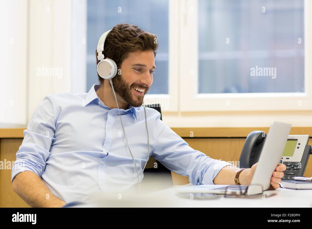 Homme barbu avec casque et portable au bureau Banque D'Images
