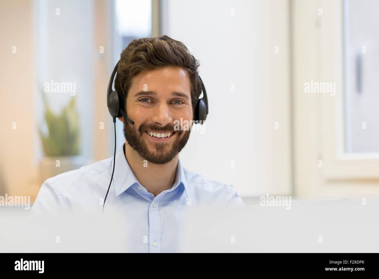 Portrait d'homme barbu avec casque au bureau Photo Stock