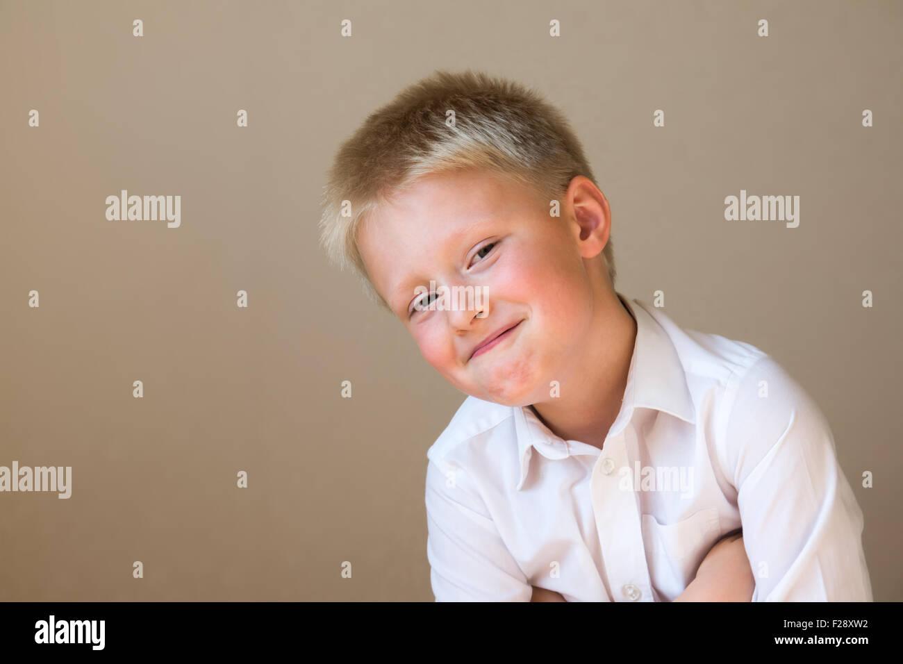 Cunning sly smiling happy enfant intelligent garçon sur fond gris Photo Stock