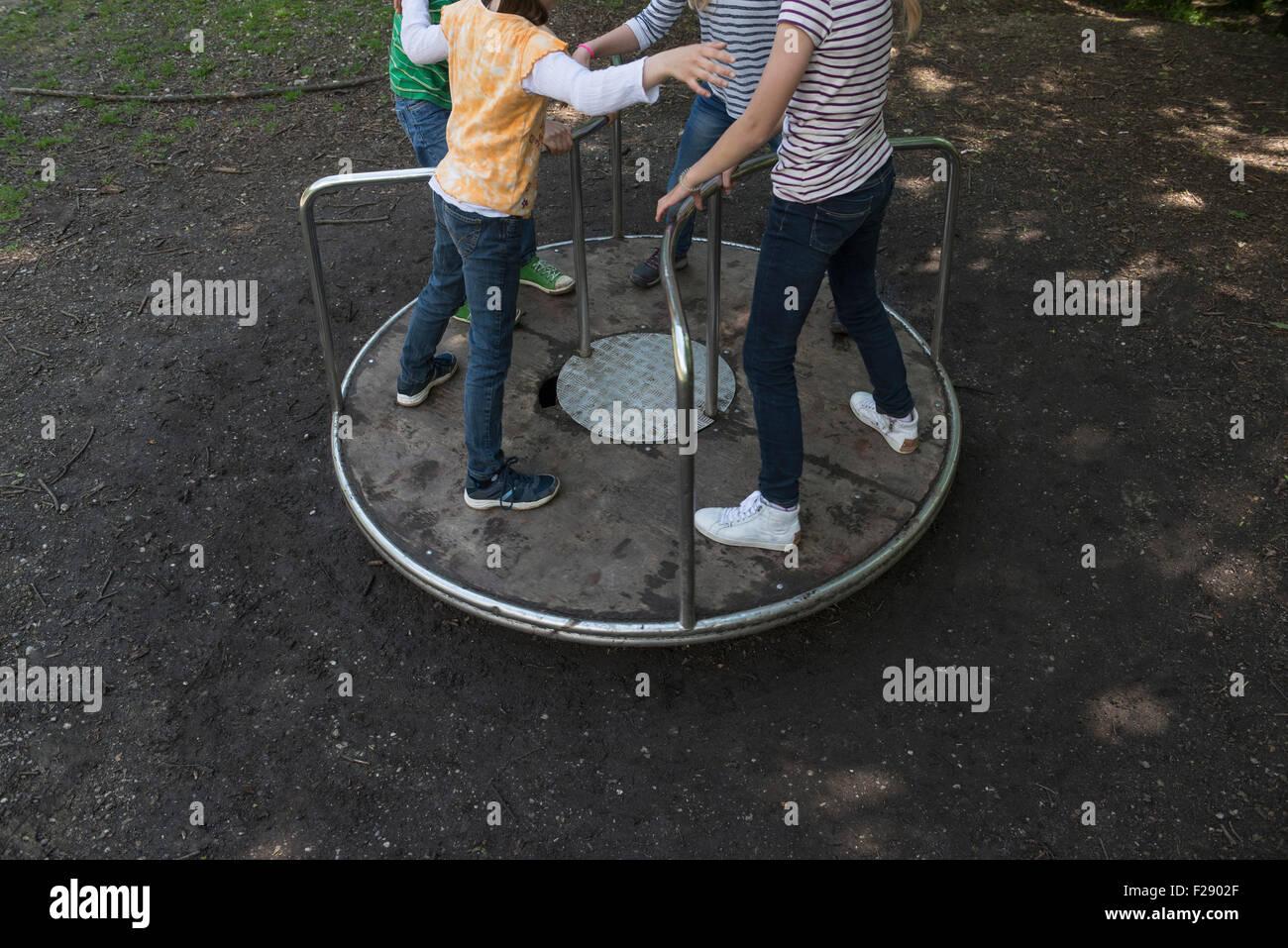 Les enfants s'amusant sur un carrousel en aire de jeux, Munich, Bavière, Allemagne Photo Stock