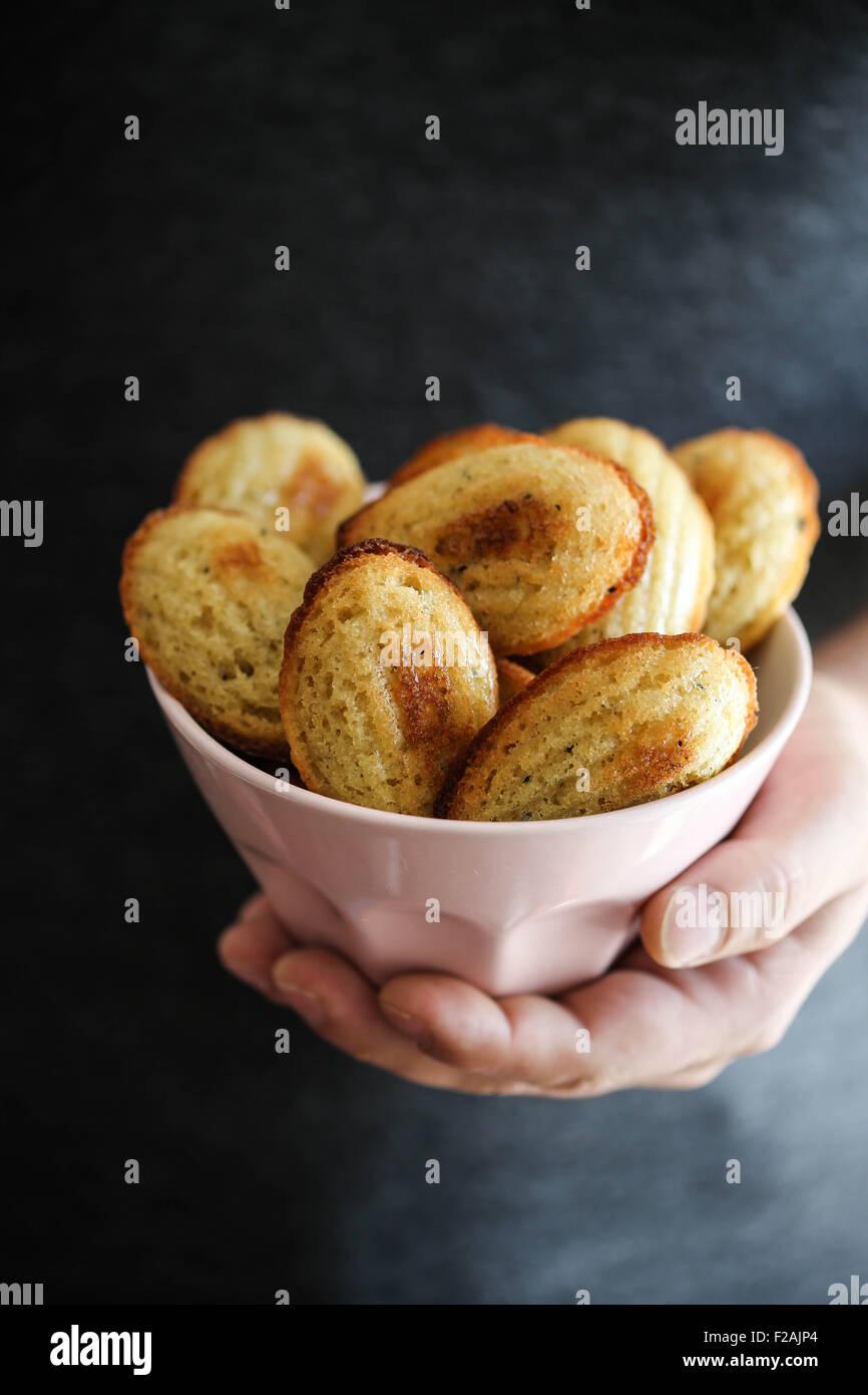 Quelqu'un qui tient un bol plein de madeleines Photo Stock