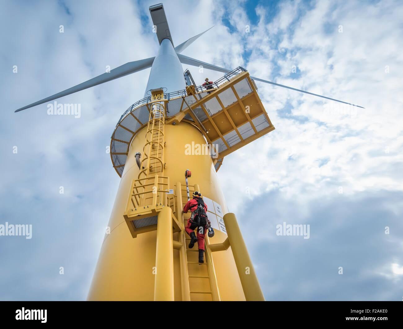 L'escalade des ingénieurs de l'éolienne parc éolien offshore au bateau, low angle view Photo Stock