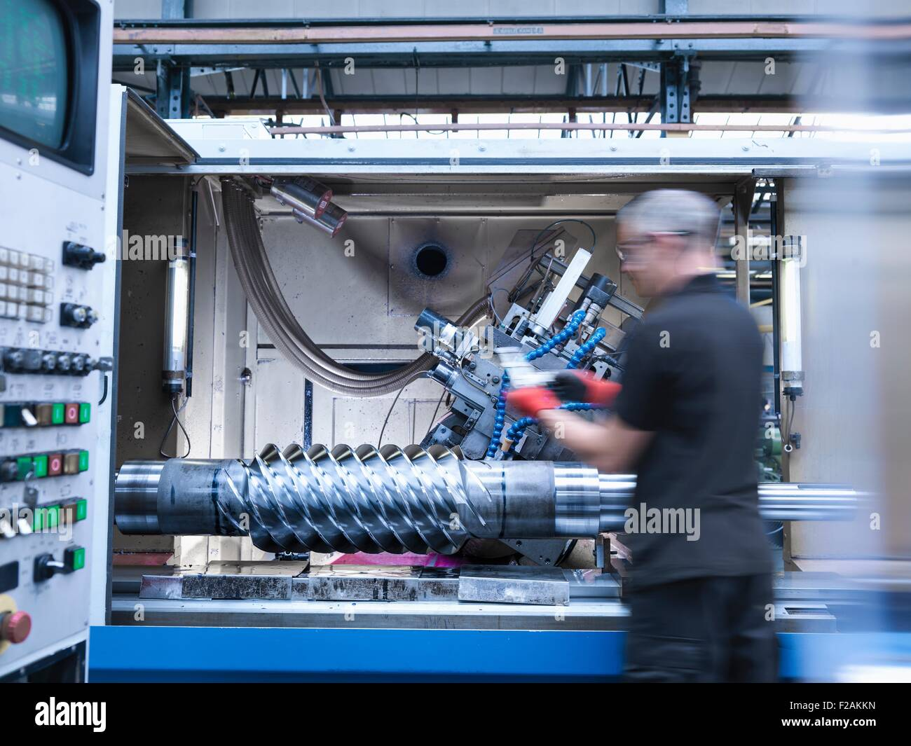 Engineer inspecting pignon d'entraînement à vis sans fin en tour dans l'usine d'ingénierie Banque D'Images