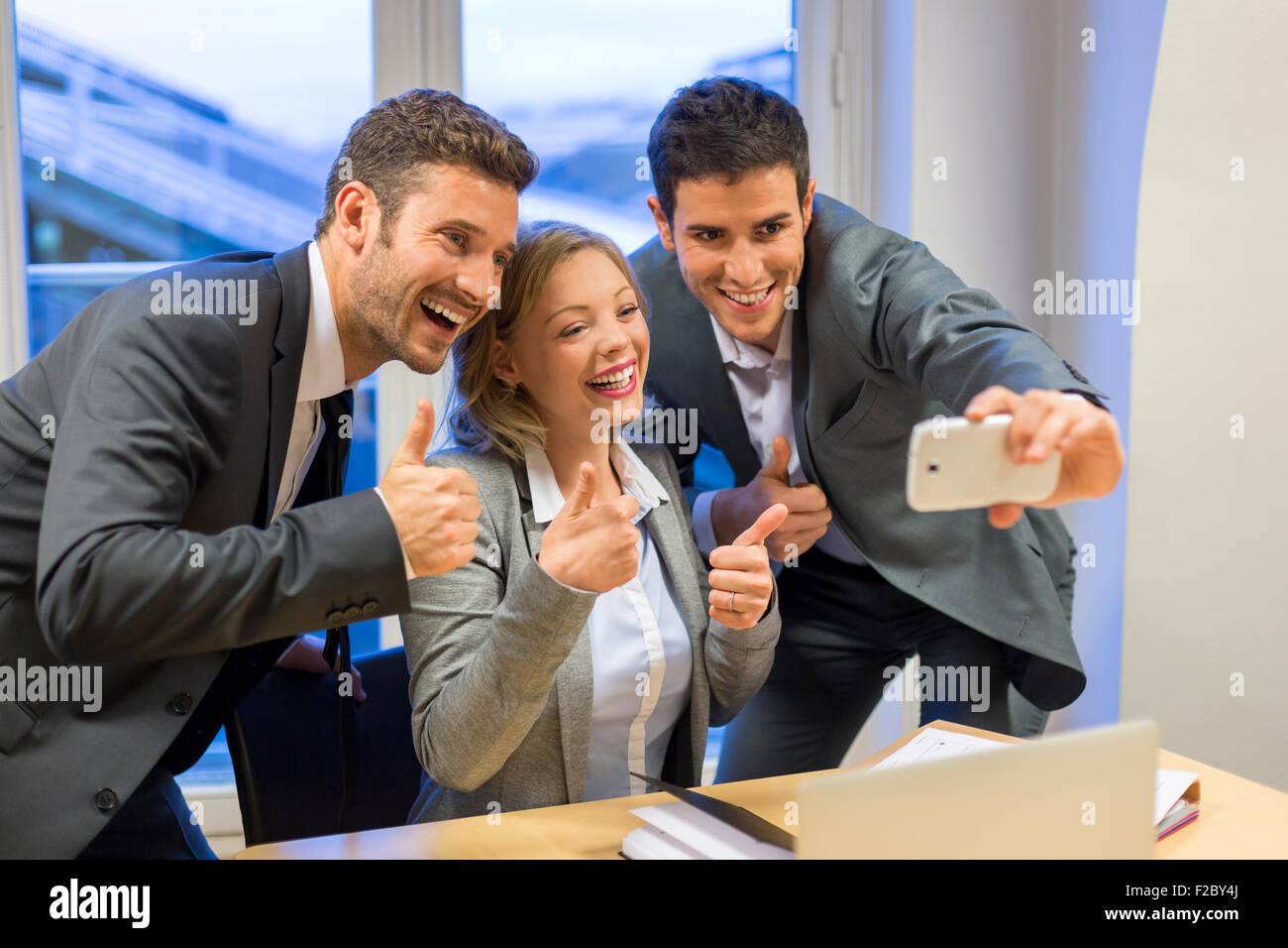 Portrait de trois hommes d'affaires faire pouce tout en tenant un smartphone avec selfies Banque D'Images