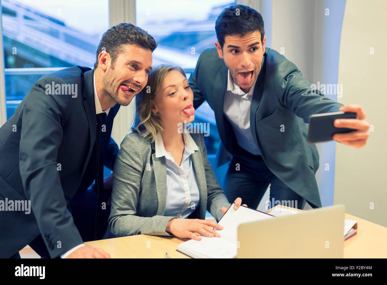 Portrait de trois personnes faisant des grimaces tout en tenant un smartphone avec selfies Banque D'Images