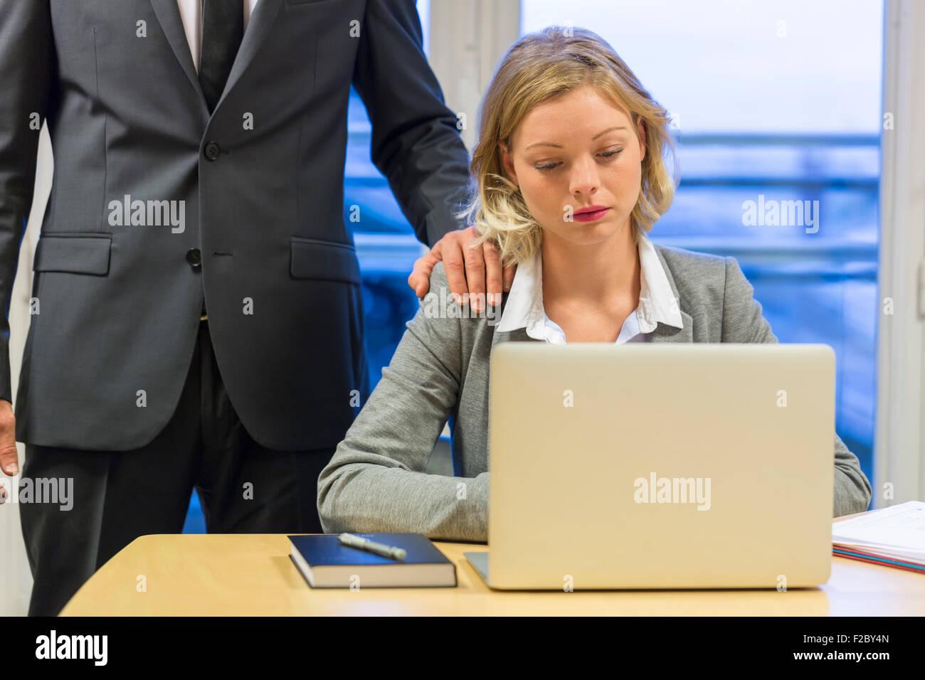 Déprimé businesswoman using laptop dans son bureau avec son collègue Banque D'Images