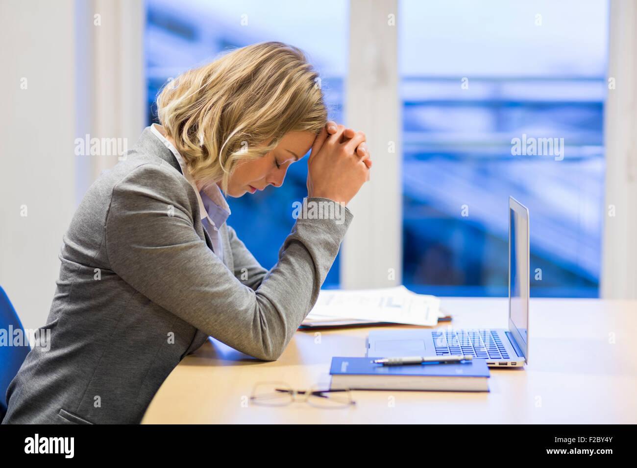 Pensive business woman sitting in office, les mains sur le front Banque D'Images