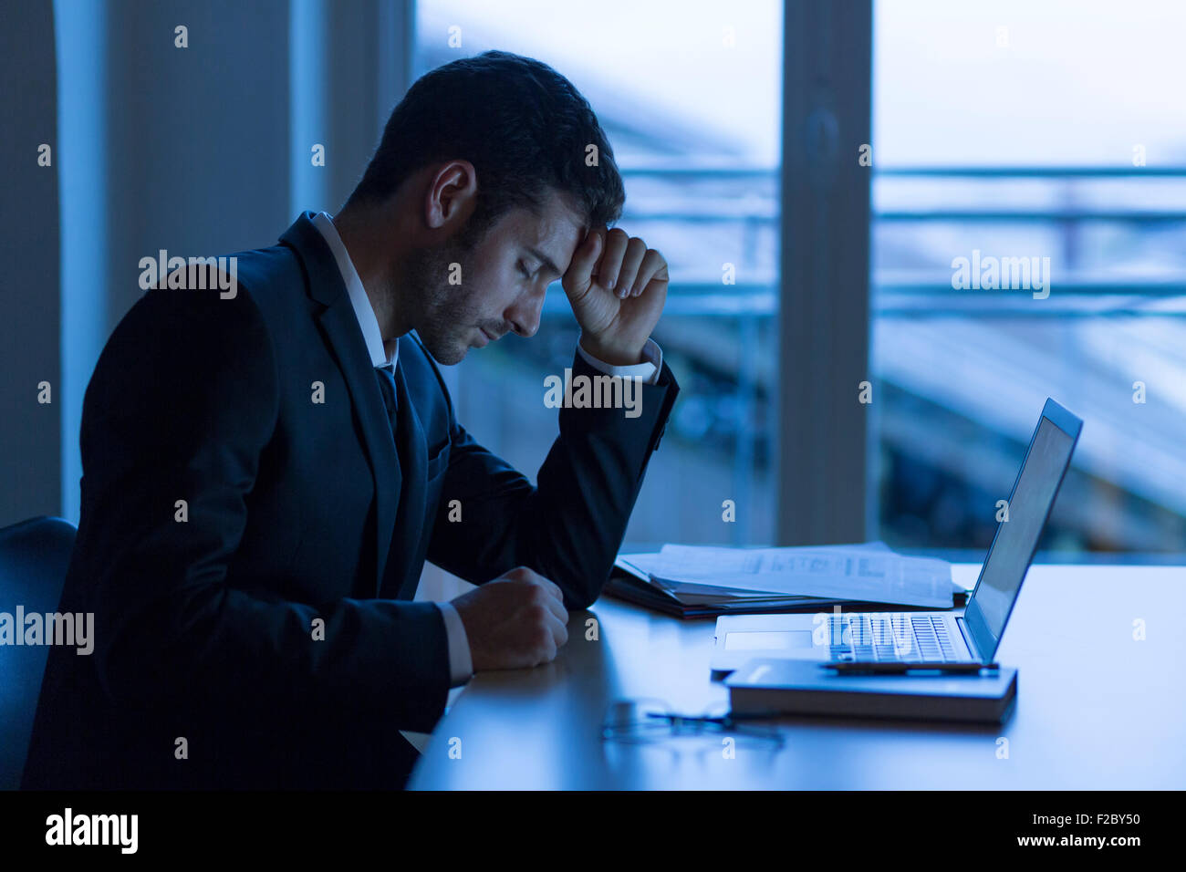 Pensive businessman sitting in darkness, poing sur front office Banque D'Images