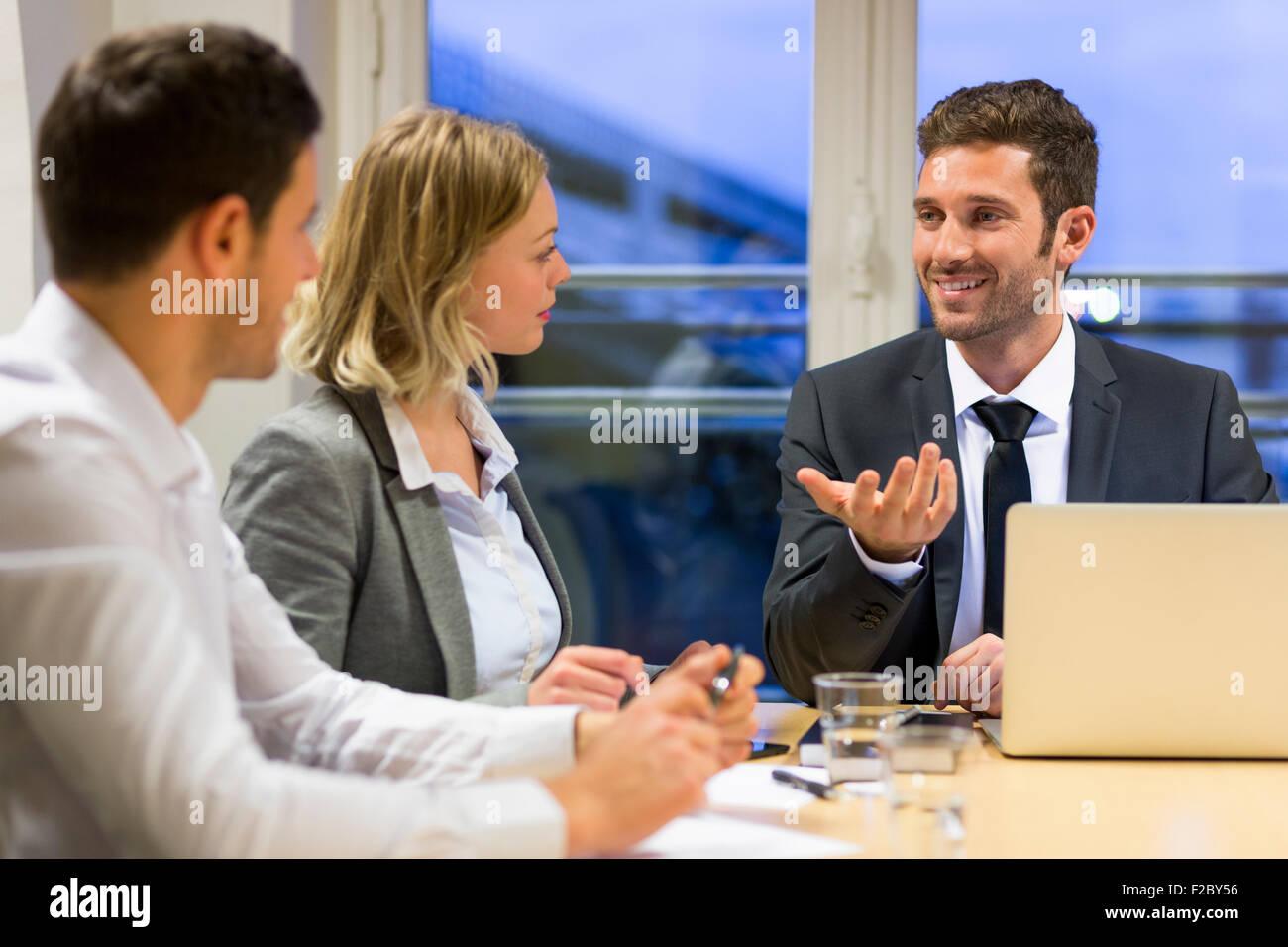 Les hommes et femmes en faisant valoir l'ensemble de table de conférence Banque D'Images