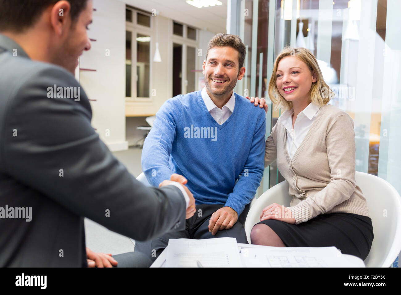 Businessman shaking hands with woman in office Banque D'Images