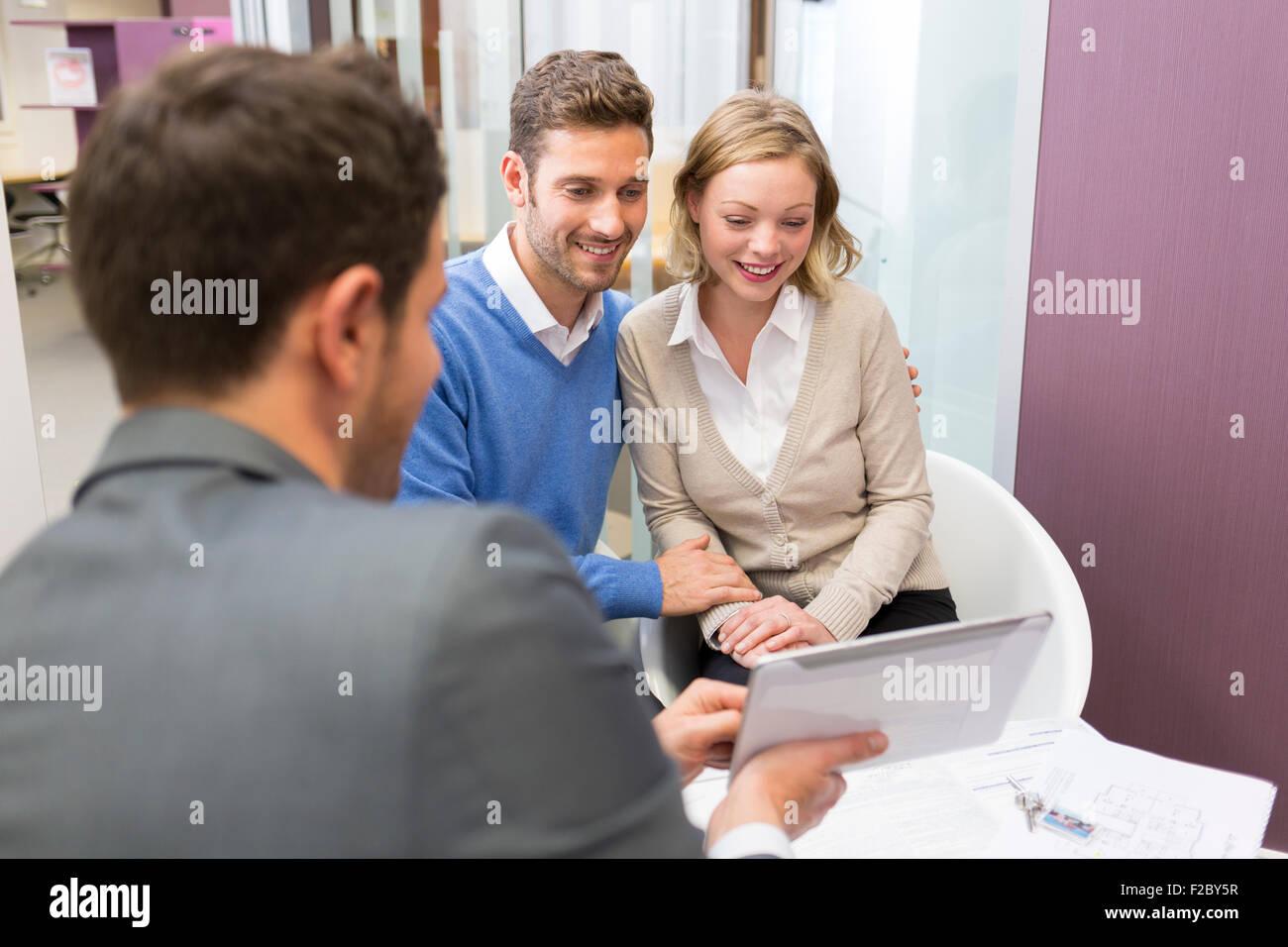 Conseiller financier à l'aide de tablette numérique et rencontre avec couple in office Banque D'Images