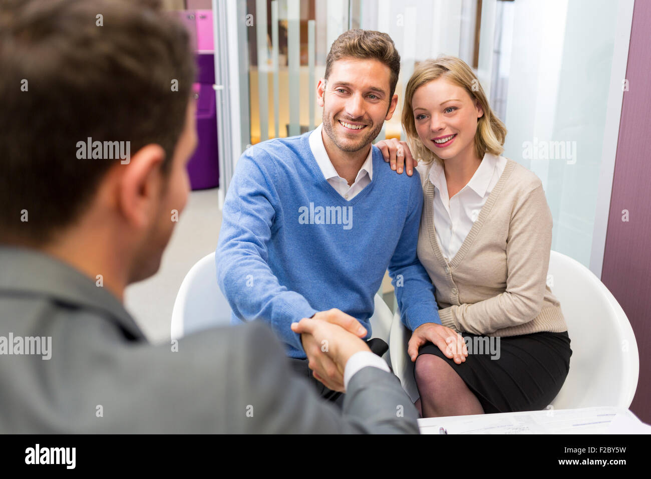 Businessman shaking hands with couple in office Banque D'Images
