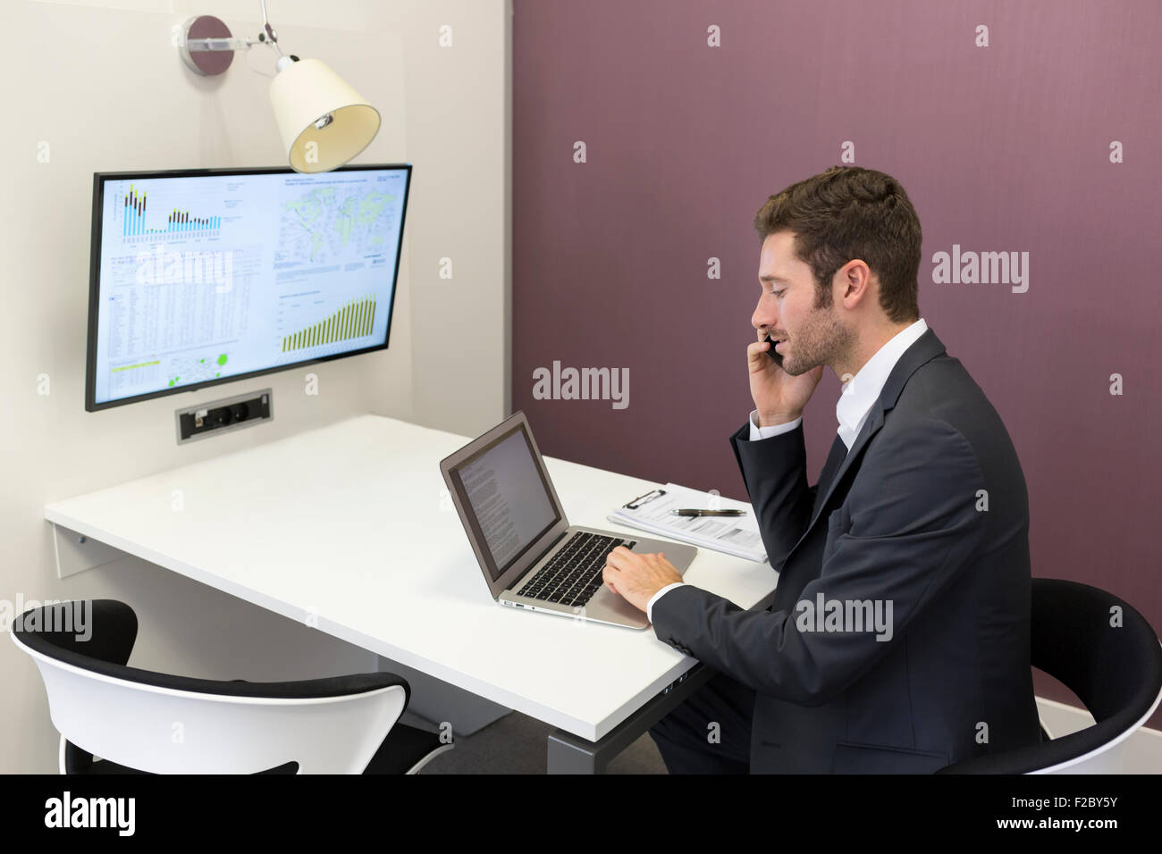 Businessman using cell phone in conference room Banque D'Images