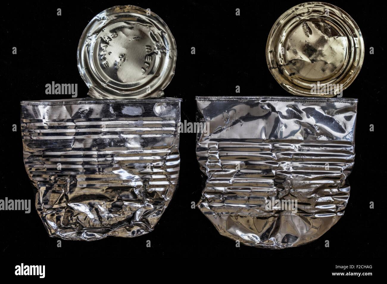 Deux canettes de métal aplati sur noir Photo Stock