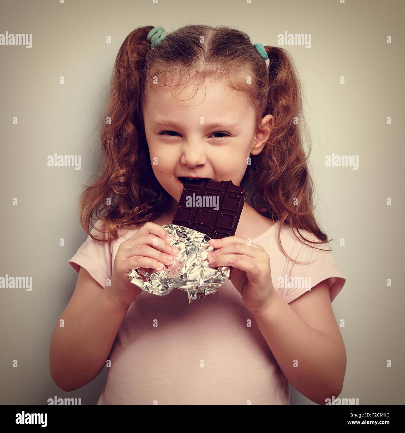 Cunning kid girl eating chocolat noir avec plaisir et regard curieux. Vintage closeup portrait Photo Stock