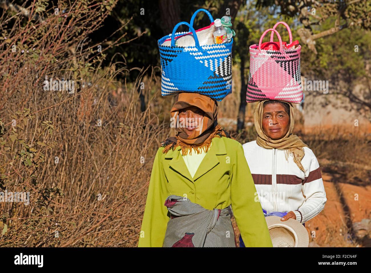 Deux femmes malgaches avec panier sur leur tête de marche marché hebdomadaire à Ambalavao, Haute Photo Stock