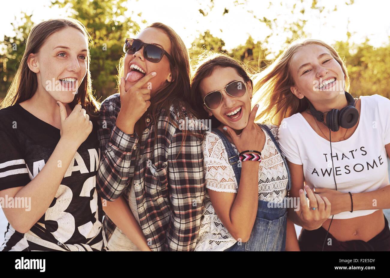 Groupe de filles faisant l'amusement des expressions un l'appareil photo, à l'extérieur dans un parc Banque D'Images