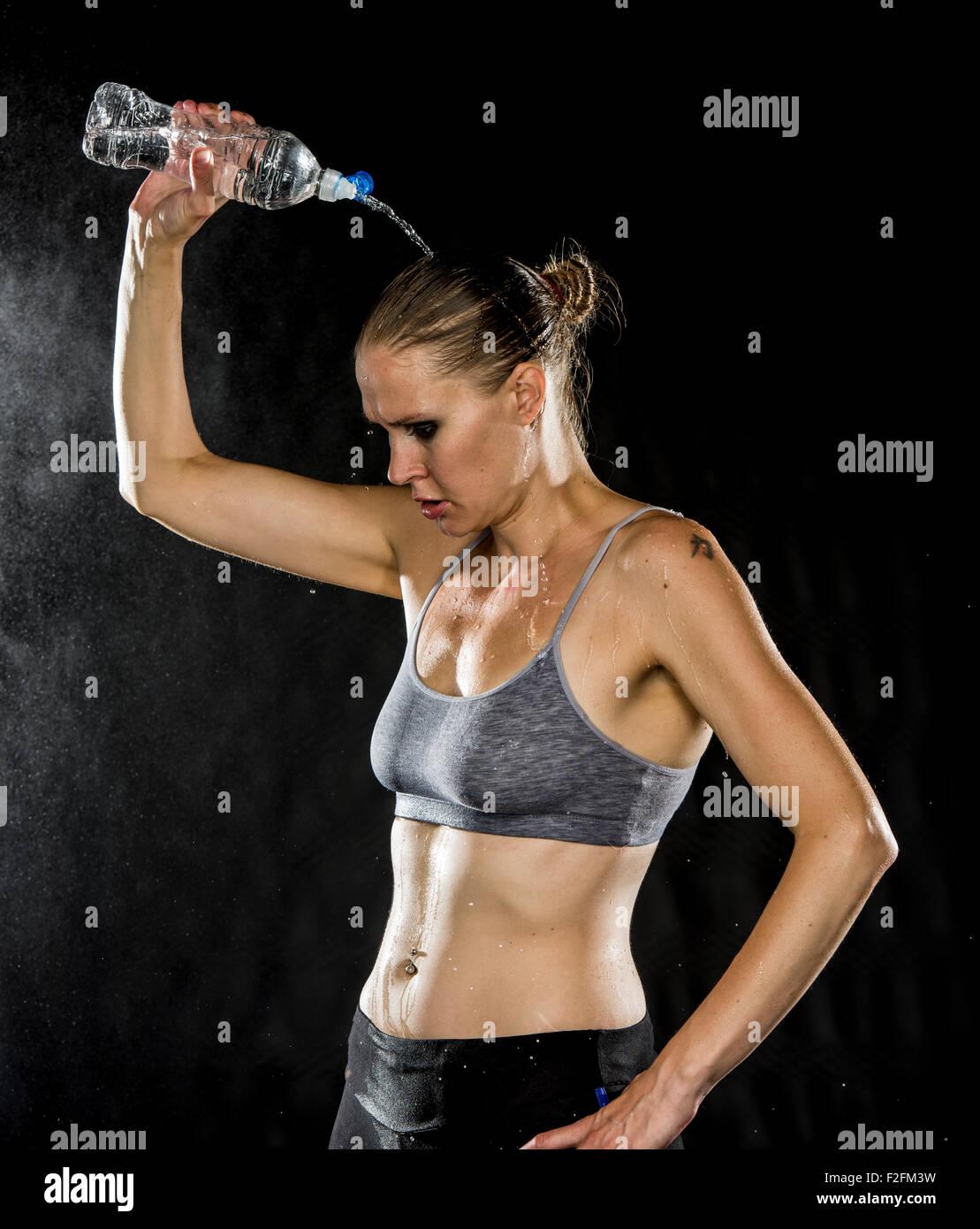 Jeune femme athlétique verser de l'eau sur la tête Banque D'Images