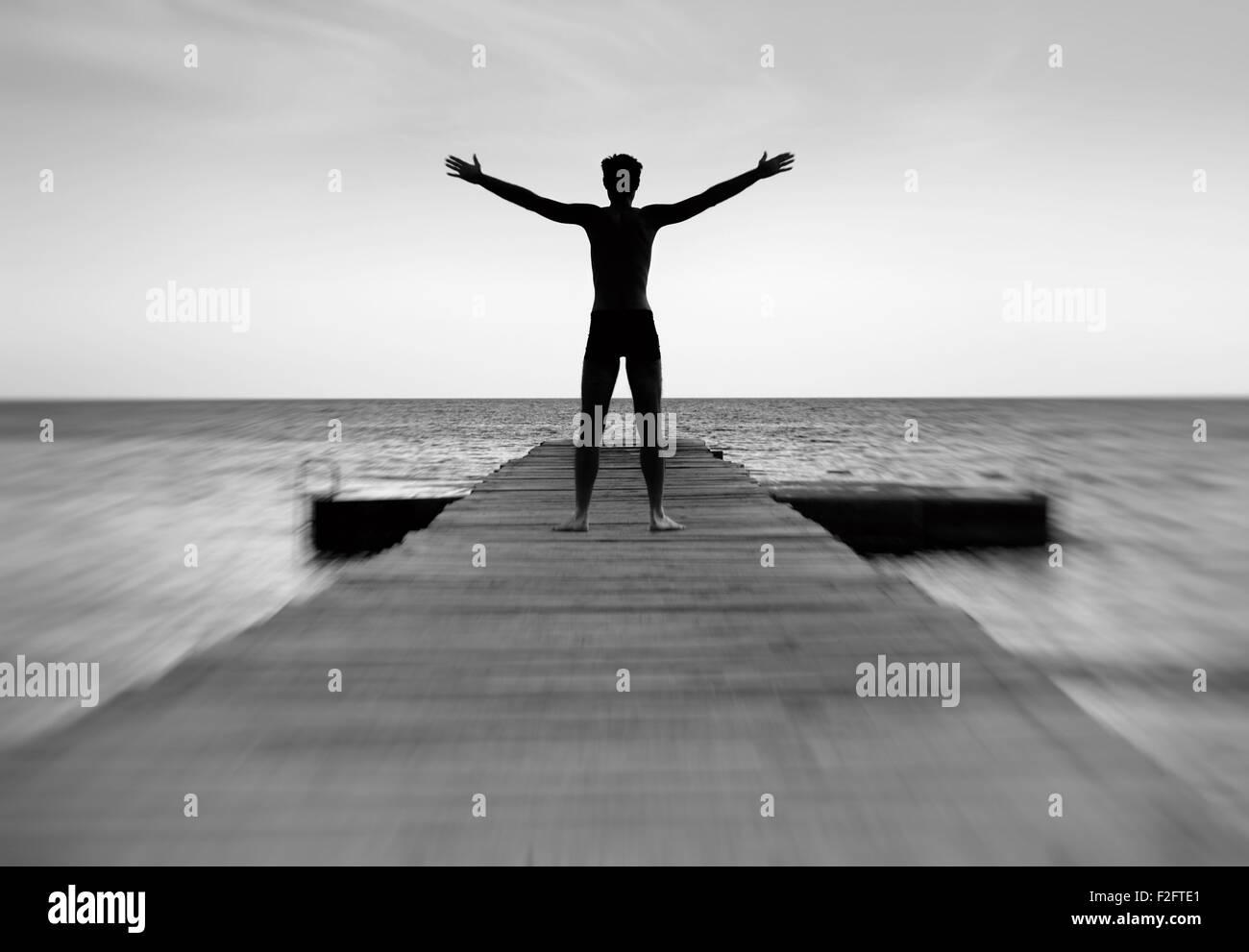 Silhouette d'un homme pacifique sur la jetée de la mer Photo Stock