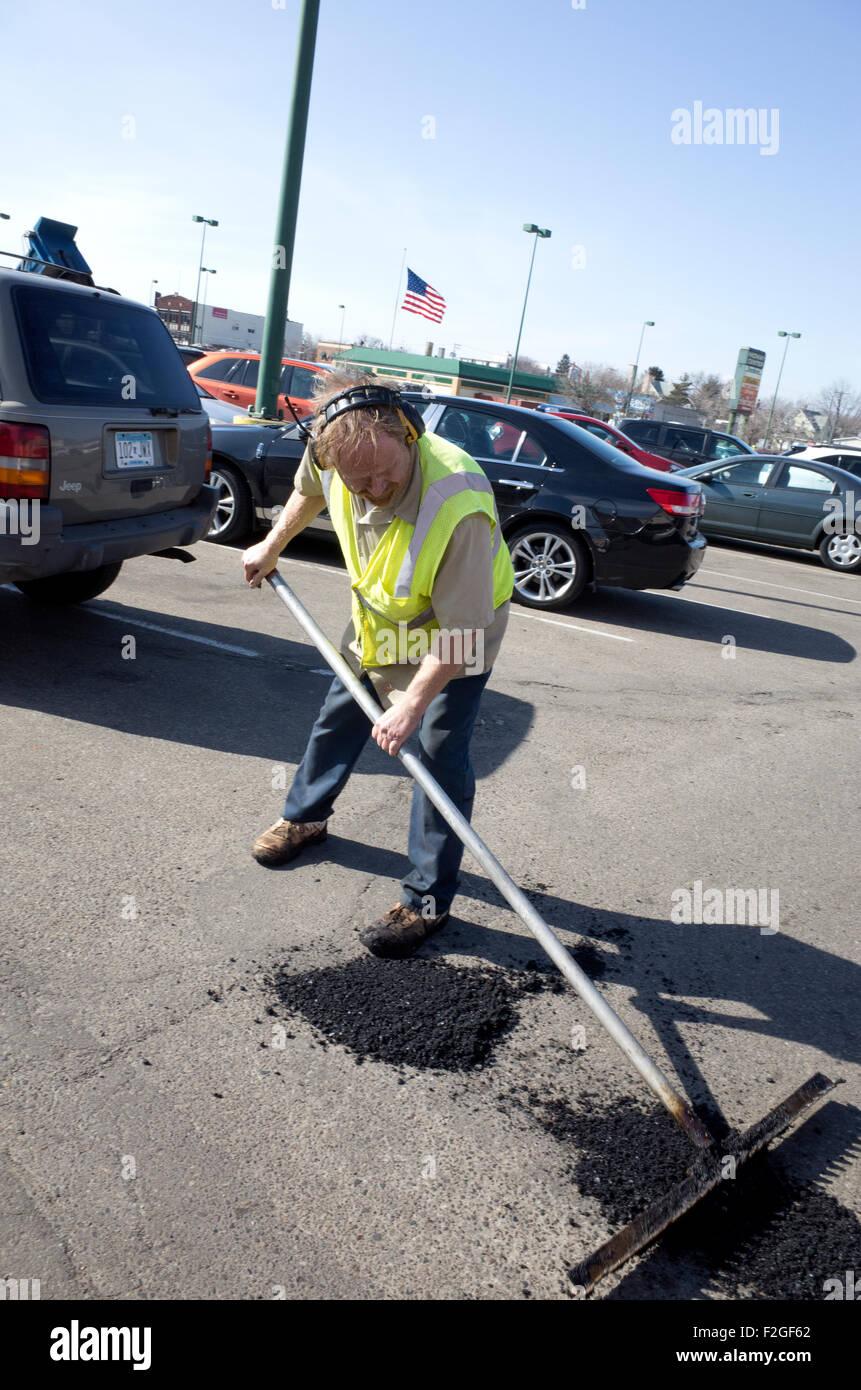 Homme d'entretien de l'asphalte sur lissage patched-de-poule dans city parking. St Paul Minnesota MN USA Banque D'Images