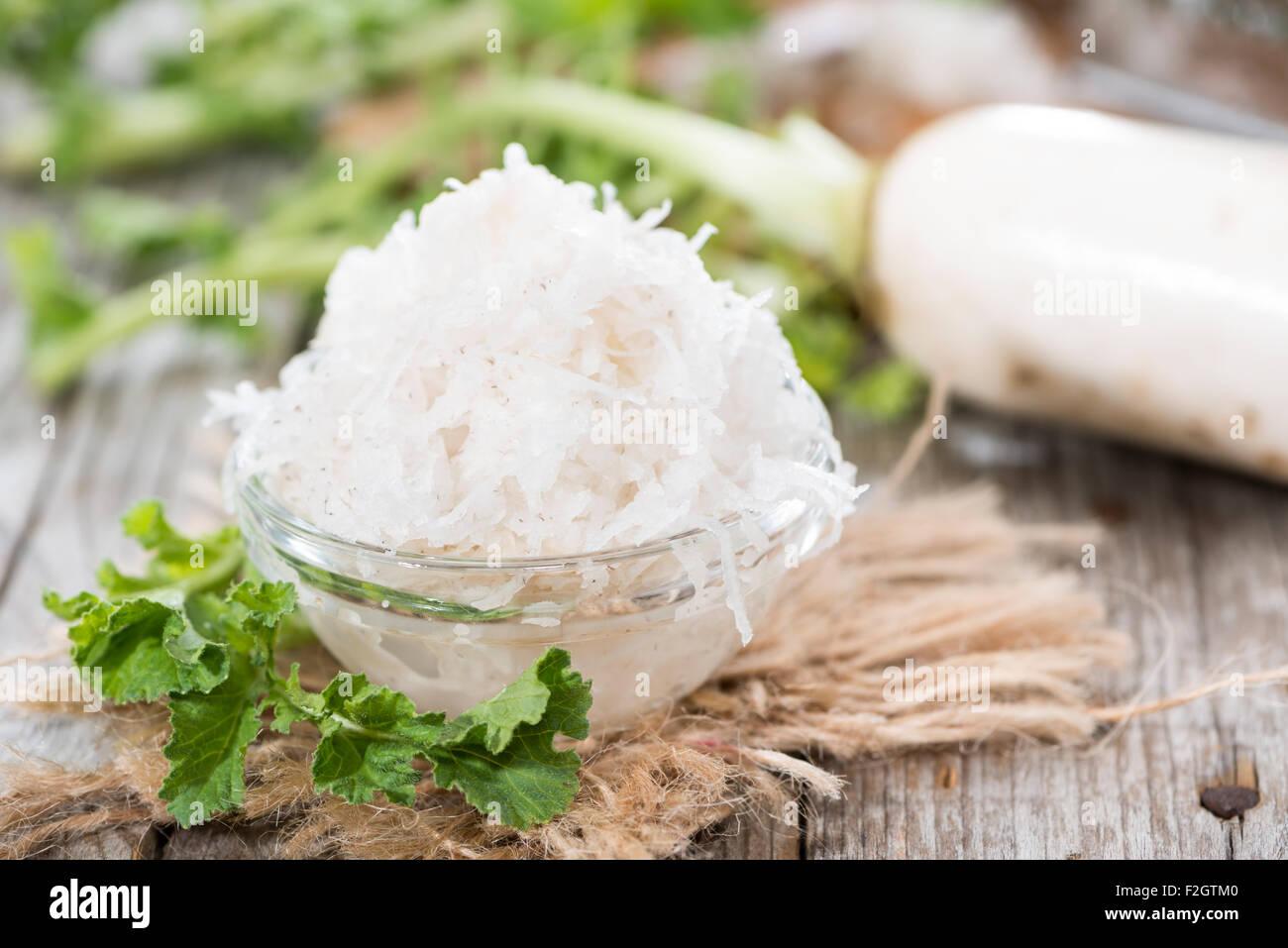 Raifort râpé frais sur fond de bois foncé Photo Stock